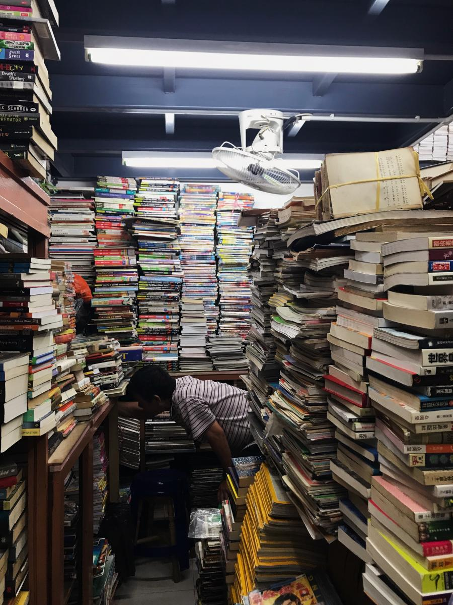 photo of a person in a space surrounded by stacks of books