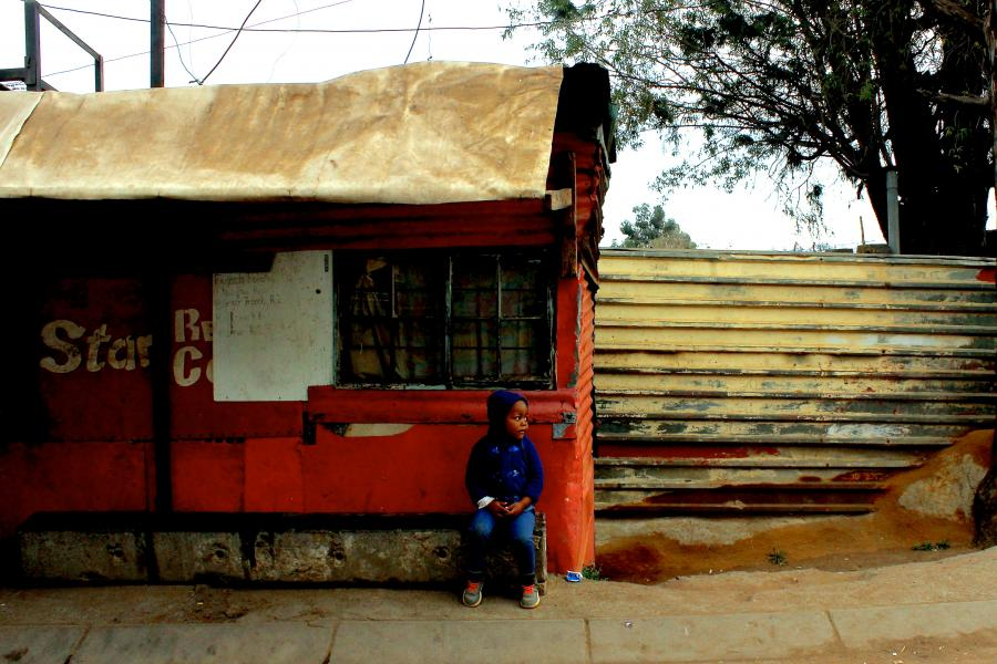 A little boy sits outside a tin building