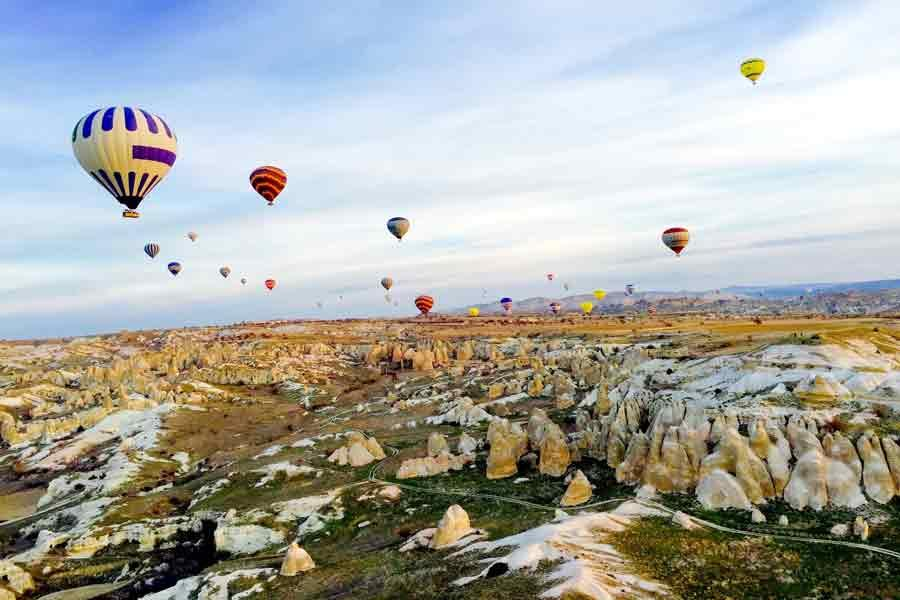 Many hot air balloons floating over rock formations