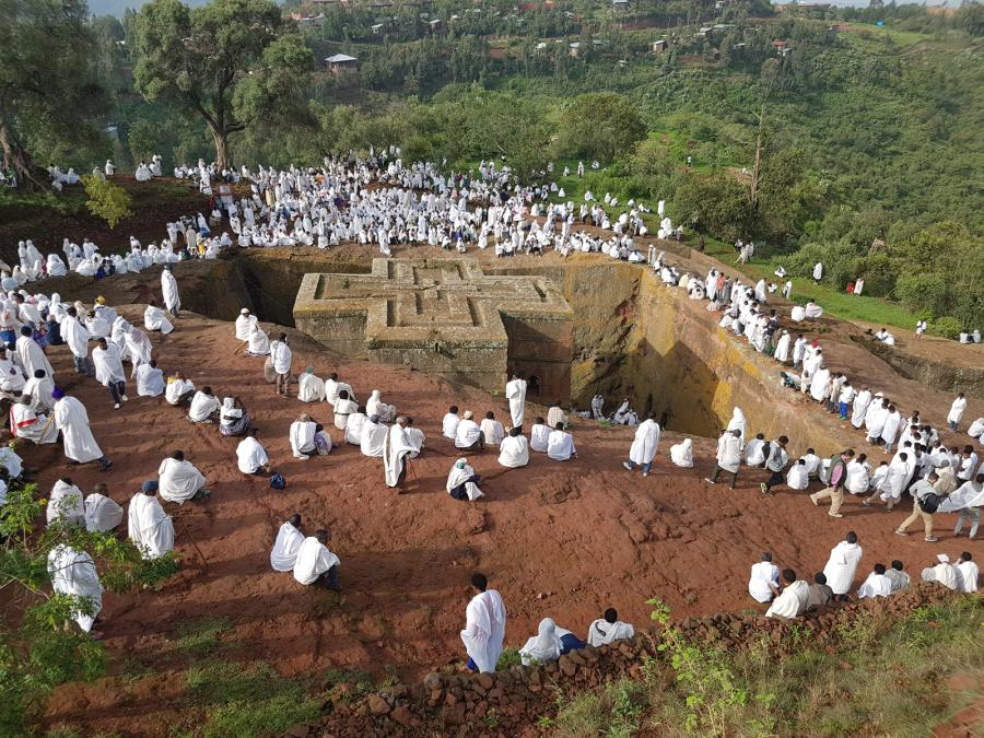 People in white-robes surround a large opening in the ground with a cross