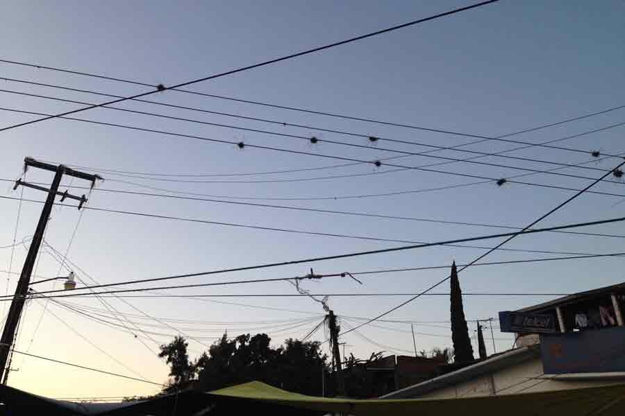 Intersecting powerlines against sky