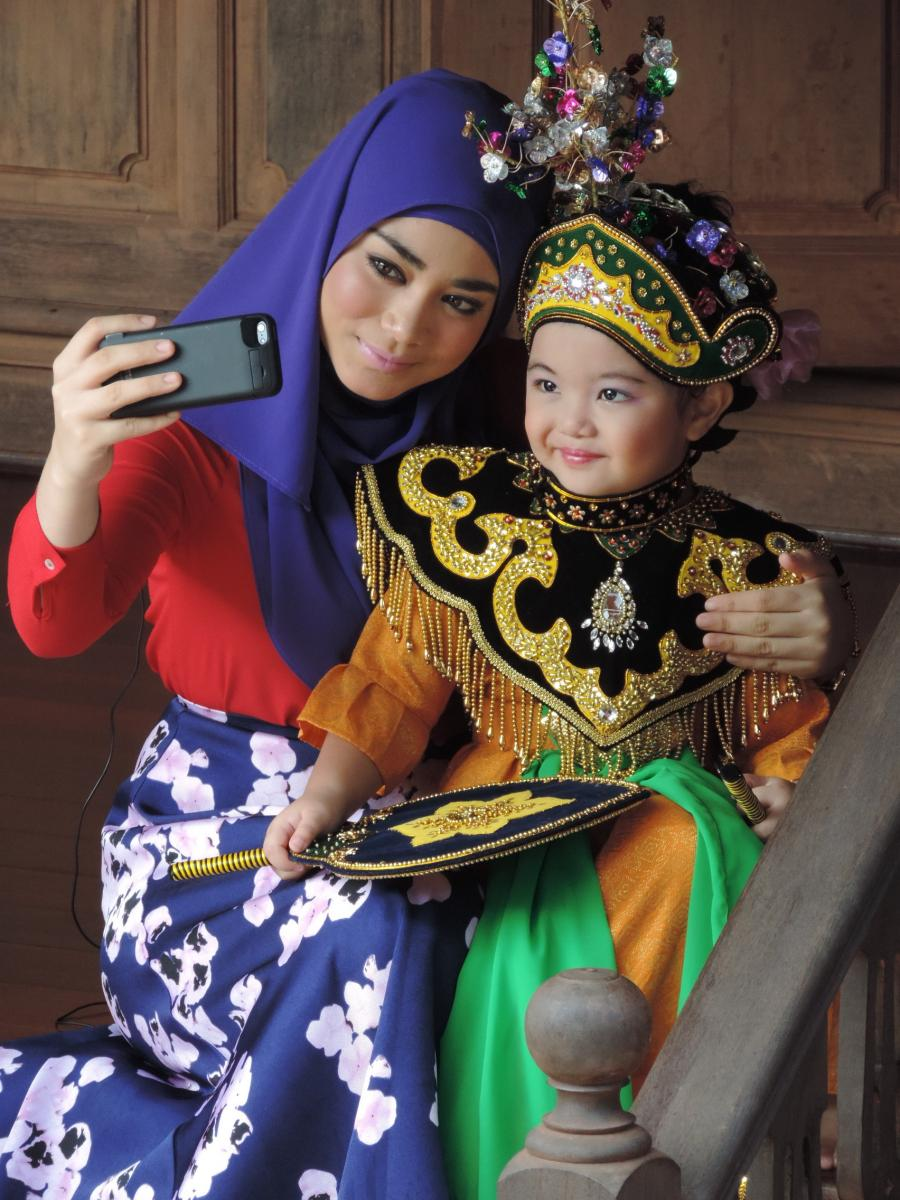 A woman poses for a selfie with a smaller girl in decorative clothing