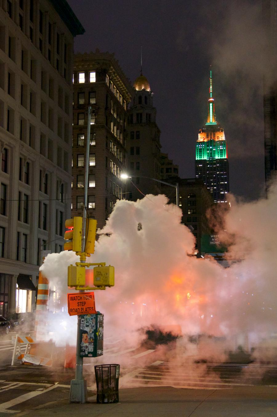 street in New York City at night with steam and construction signage