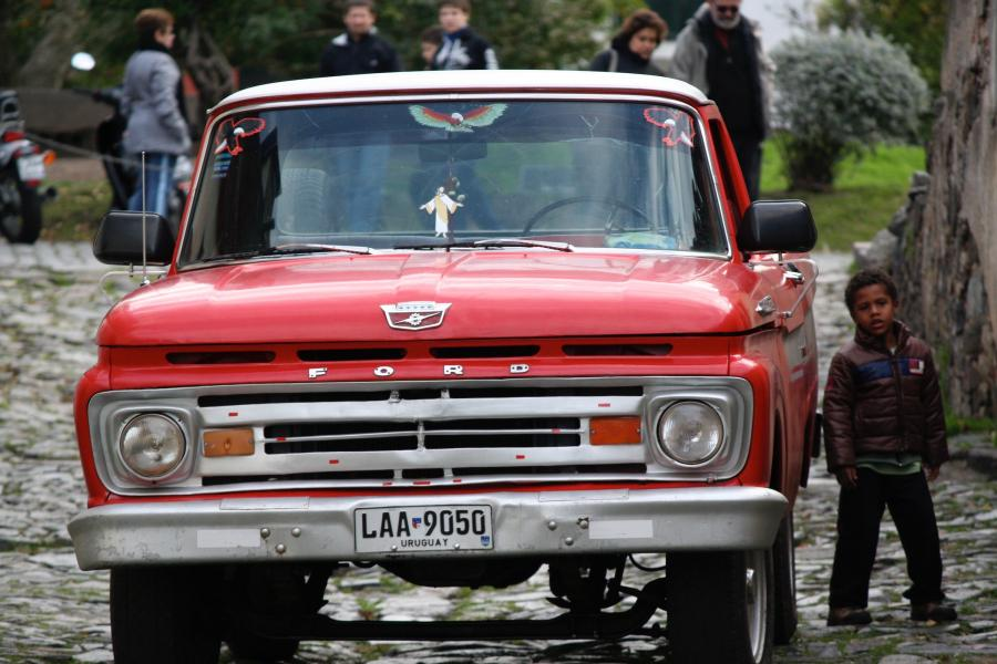 A little boy stands beside a bright red pickup truck