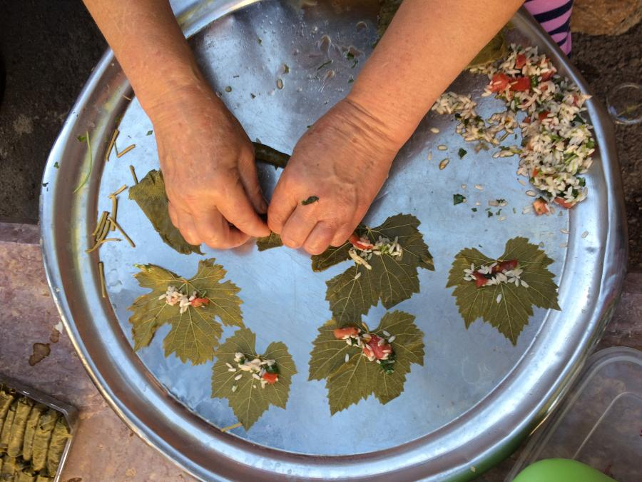 a persons hands preparing grape leaves and rice over a metal tray