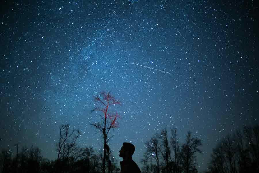 A person's silhouette against a dark sky filled with stars and a comet